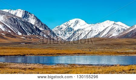 Snowy mountains reflected in lake. Severe mountains peaks covered by snow. Russia, Siberia, Altai mountains, Chuya ridge.