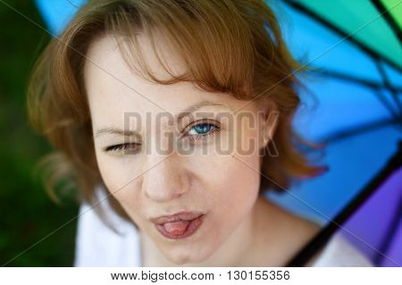 Portrait of funny girl which is having fun and showing tongue one eye is squinted on multicolored umbrella background. Merriment and good mood concept