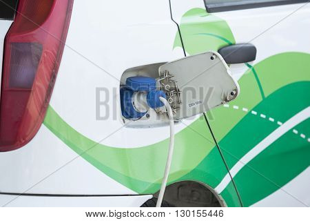 Power supply plugged into an electric car being charged