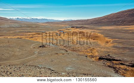 A highland river valley with yellow grass on a background of snow covered mountains and glaciers under clouds and blue sky Altai mountains Siberia Russia