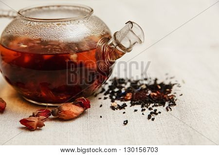 The Dry Red Small Roses with Black Tea in the Glass Teapot,Tea Drinking,Aromatized Flowers, Rough Linen Tablecloth