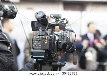 Filming an event with a video camera.