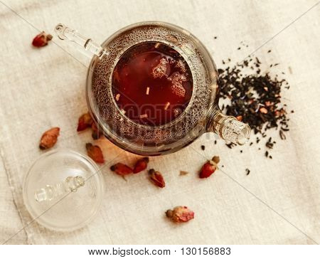 The Dry Red Small Roses with Black Tea in the Glass Teapot,Tea Drinking,Aromatized Flowers,Table Rough Linen Tablecloth;Top View