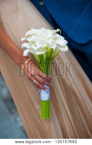 white wedding bouquet of calla in hands of the bride.