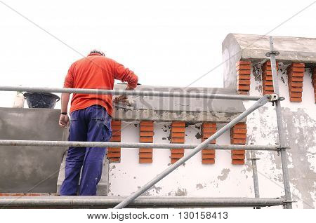 A Unrecognizable builder applying cement on wall