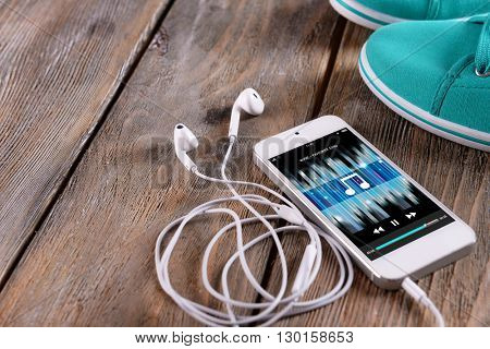 White smart phone with headphones and gumshoes on wooden background