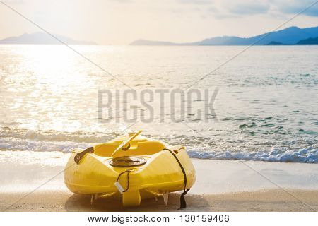Kayak on tropical beach in sunset with bright sunlight