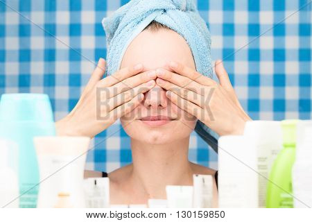 Young white-skinned girl with towel on head has covered her eyes by hands in bathroom. Skincare and beauty concept. Frontal portrait
