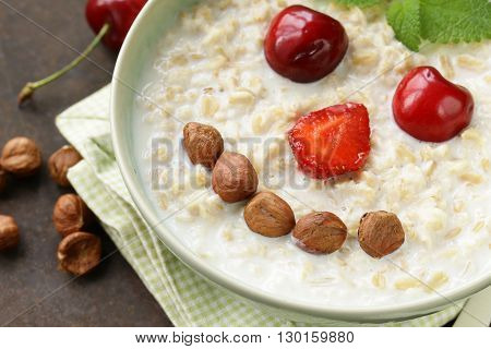 oatmeal porridge with milk and berries - healthy, funny breakfast