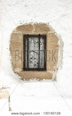 Small window with metal bars and mesh in the whitewashed wall