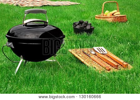 Portable Bbq Grill Appliance And Tools On The Fresh Lawn