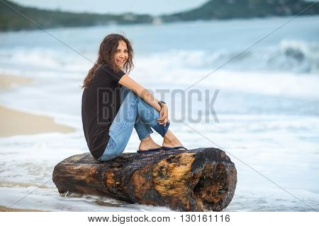 happy laughing woman sitting on the beach