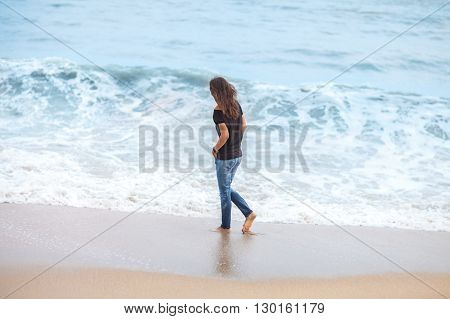 beautiful woman walking along tropical sea in storm