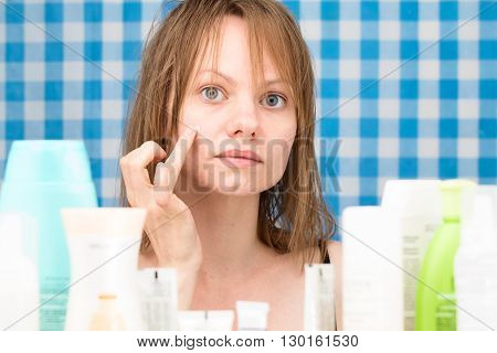 Girl is applying cosmetic product on her problem skin areas in bathroom. Skincare and beauty concept. Frontal portrait