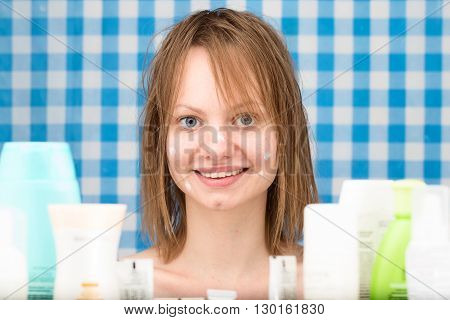 Girl without make-up with points of cosmetic product on her face is smiling surrounded by variety of cosmetics in the bathroom. Front portrait. Skin care and beauty concept