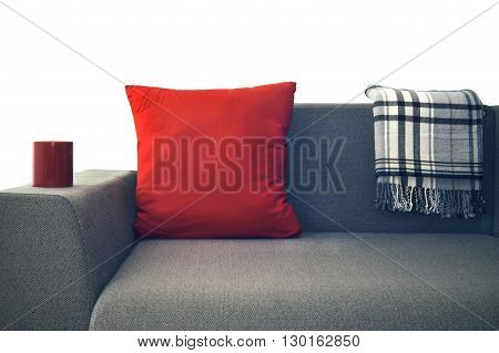 red pillow and a plaid on a gray couch