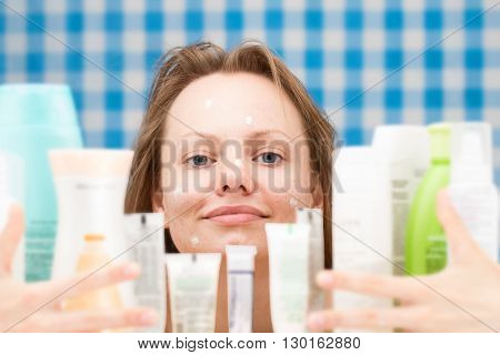 Contented girl is embracing various cosmetics in bathroom