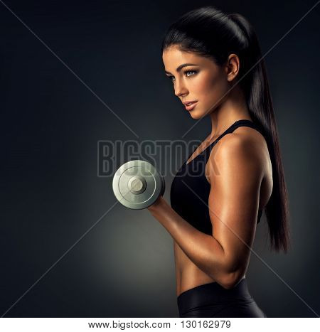 Happy and beautiful fitness woman lifting dumbbells . Fitness sporty woman showing her well trained body . A beautiful girl's body with rippling muscles from strength training .