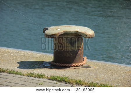 rusty mid size bollard in a port