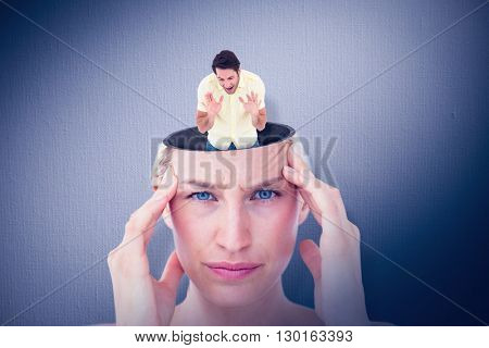 Angry man shouting at the floor against digital image of gray wall
