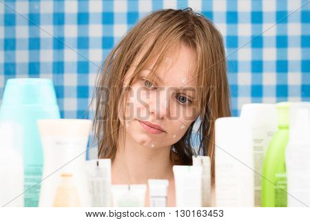 Young white-skinned girl with wet hair without makeup is looking at cosmetic products in bathroom. Skincare and beauty concept. Frontal portrait