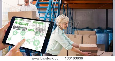 Man using tablet pc against warehouse managers loading a trolley