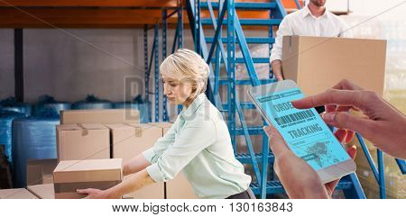 Cropped hand using smartphone against warehouse managers loading a trolley