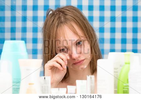 Young white-skinned girl with problem skin is weeping in bathroom in front of cosmetic products on blue-white curtains background