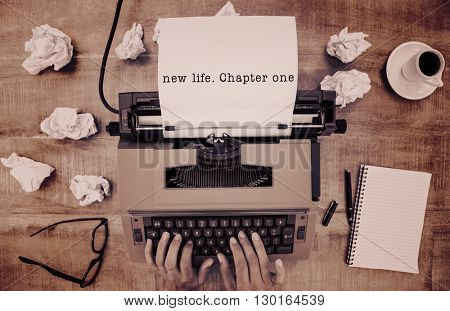 New life chapter one message on a white background against above view of old typewriter