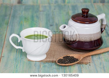 green tea with milk or hot matcha latte on wood