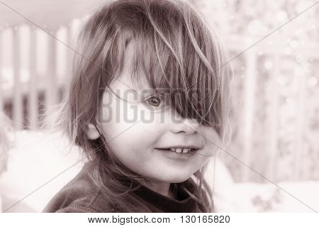 Portrait of a smiling little girl with hair on her left eye in black whote tones