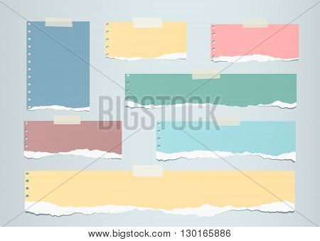 Pastel colorful ripped blank note paper are stuck on gray  background.