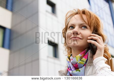 Young European fair-haired girl is talking by phone smiling and looking up on administrative building background