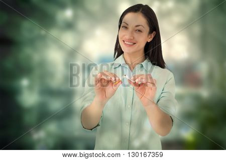 Smiling woman snapping cigarette in half against working desk in a office