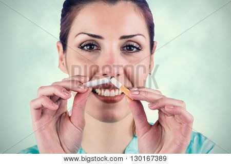 Close-up portrait of smiling woman holding cigarette against blue background