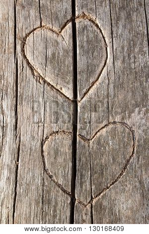 Symbol of heart and love on old wooden surface speckled with cracks