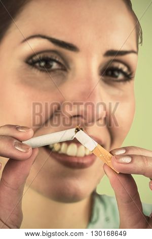 Close-up portrait of happy woman holding cigarette against green background