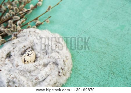 White fluffy nest with pussy-willow twigs and quail egg on closeup, side view