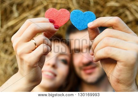 Couple of lovers is holding in their hands red and blue hearts and looking at them on hay background