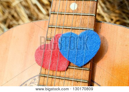 Two heart symbol red and blue together under the strings of the guitar. The concept of combining romance and musical creativity