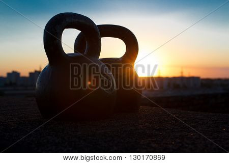 Pair of black one-pood kettlebells at sunset background over the city. Concept of access for health improvement and physical development in free time after busy day