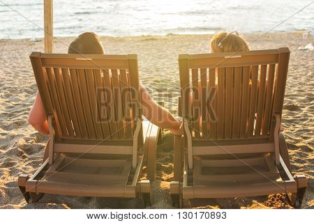 a couple sitting on the lounge chairs