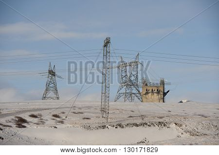 Electric cables and pylon towers on the snow covered land during winter in Iceland