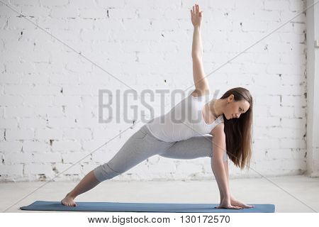 Side View Portrait Of Happy Woman Doing Extended Side Angle Pose