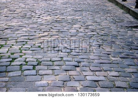 background image of old road paved with granite stones