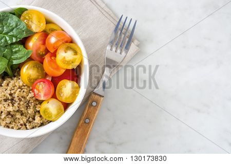 Quinoa with vegetables on white marble table