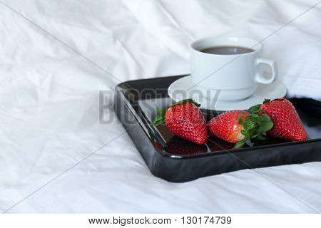 breakfast of strawberries and a cup of coffee on a black tray