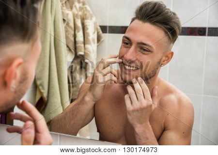 Close-up of topless young man looking in mirror at his smile in bathroom
