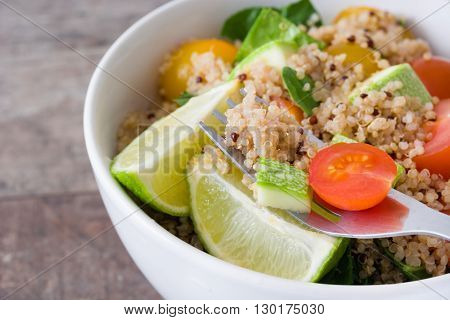 Quinoa salad with tomato and zucchini on a fork