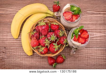 Smoothies with oatmeal strawberry, banana in glass jars on a wooden background.